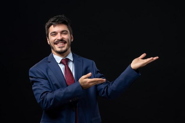 Młody uśmiechnięty mężczyzna w garniturze wskazujący coś po lewej stronie na odizolowanej ciemnej ścianie