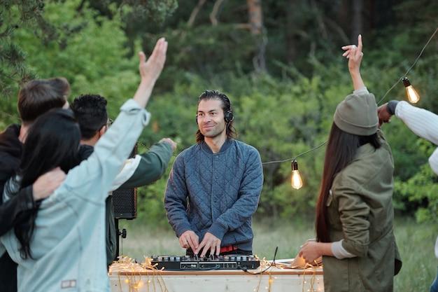 Młody uśmiechnięty mężczyzna w kurtce i słuchawkach tworzenia muzyki przed tłumem przyjaciół, tańczących i korzystających z letniego weekendu