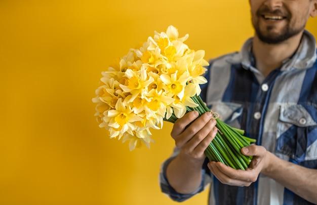 Młody uśmiechnięty mężczyzna z bukietem wiosennych kwiatów. pojęcie pozdrowienia i dzień kobiet.