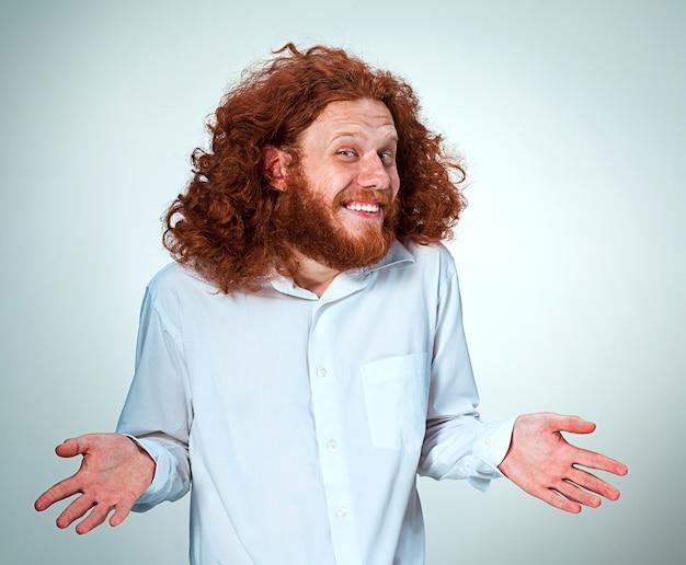 Młody uśmiechnięty mężczyzna z długimi rudymi włosami patrząc na kamery