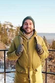 Młody uśmiechnięty mężczyzna z plecakiem stojący przed kamerą na tle drzew i skał pokrytych śniegiem i czystym błękitnym niebem w zimowy dzień