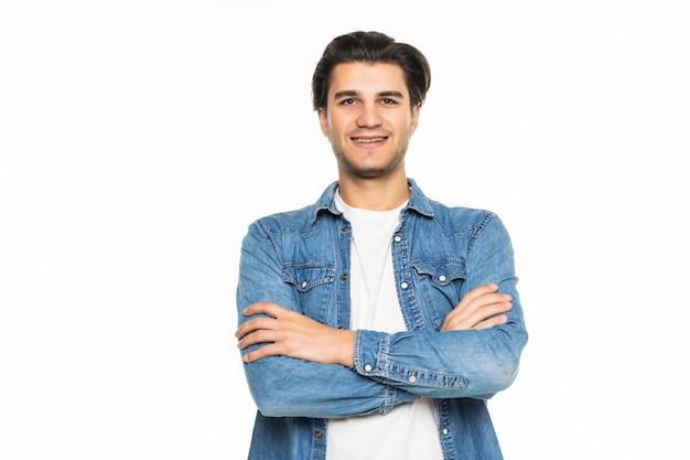 Młody uśmiechnięty mężczyzna ze skrzyżowanymi rękami na białym