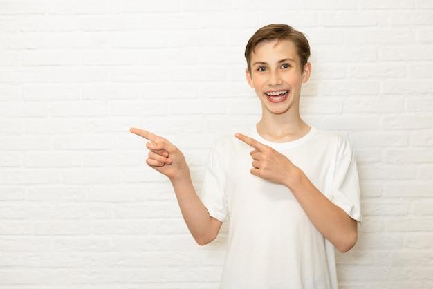 Młody uśmiechnięty nastolatek chłopiec pokazuje palcem z boku