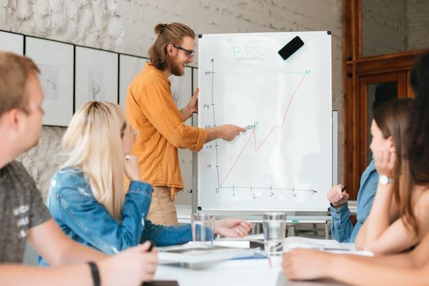 Młody uśmiechnięty nauczyciel stojący w pobliżu tablicy i szczęśliwie pokazując uczniom schemat. grupa młodych uczniów słucha nauczyciela podczas lekcji