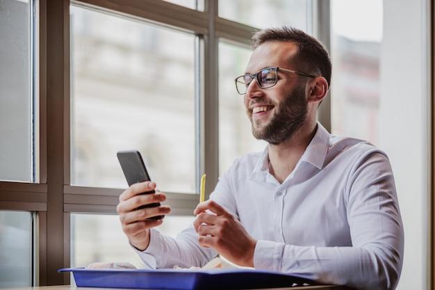 Młody uśmiechnięty naukowy mężczyzna elegancko ubrany siedzi w restauracji typu fast food, używając smartfona i jedząc frytki.