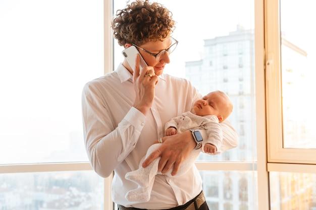 Młody uśmiechnięty ojciec biznesmen bawi się ze swoim małym synkiem podczas rozmowy przez telefon komórkowy w domu