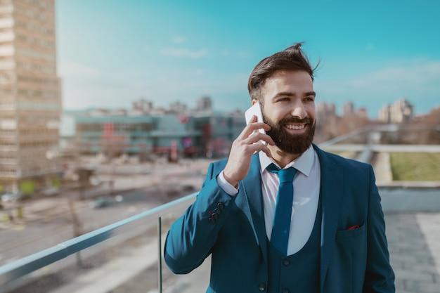 Młody uśmiechnięty perspektywiczny brodaty biznesmen w kostiumu ma biznesowego wezwanie