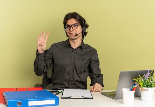 Młody uśmiechnięty pracownik biurowy mężczyzna na słuchawkach w okularach optycznych siedzi przy biurku z narzędziami biurowymi za pomocą gestów laptopa cztery znaki dłoni na białym tle na zielonym tle z przestrzenią do kopiowania