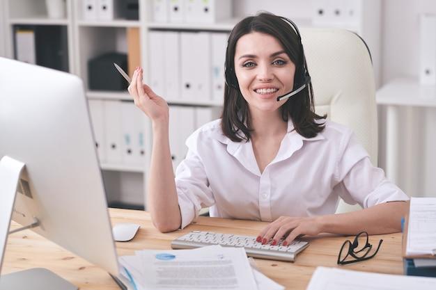 Młody uśmiechnięty przedstawiciel obsługi klienta patrzy na ciebie siedząc przy miejscu pracy przed ekranem komputera i konsultując się z klientami