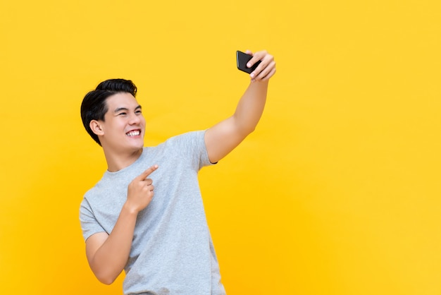 Młody uśmiechnięty przystojny azjatycki mężczyzna bierze selfie z smartphone