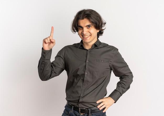 Młody uśmiechnięty przystojny kaukaski mężczyzna wskazuje w górę i kładzie rękę na talii na białym tle na białym tle z miejsca na kopię