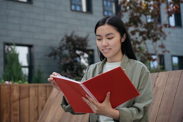 Młody uśmiechnięty student studiujący czytanie książki w kampusie uniwersyteckim powrót do koncepcji edukacji szkolnej