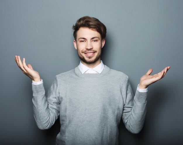 Młody uśmiechnięty szczęśliwy biznesowy mężczyzna pokazuje coś na szarej przestrzeni