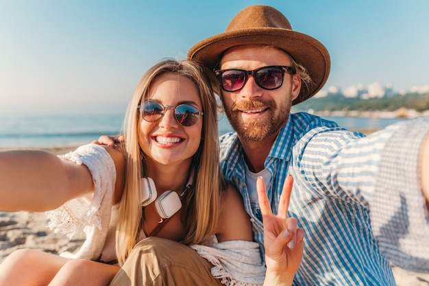 Młody uśmiechnięty szczęśliwy mężczyzna i kobieta w okularach przeciwsłonecznych siedzi na piaszczystej plaży, biorąc zdjęcie selfie na aparat w telefonie