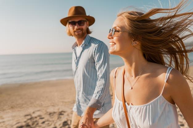Młody uśmiechnięty szczęśliwy mężczyzna w kapeluszu i blond kobieta razem biegnie na plaży na wakacje w podróży