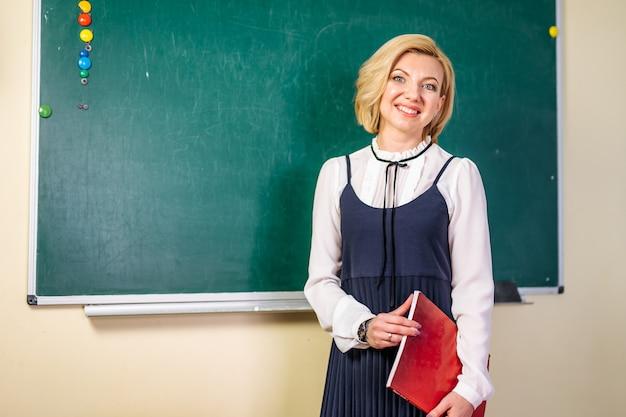 Młody uśmiechnięty uczeń lub nauczyciel przy blackboard