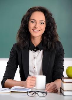 Młody uśmiechnięty uczeń lub nauczyciel przy blackboard.