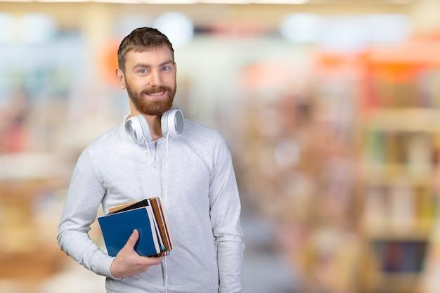 Młody uśmiechnięty uczeń z książkami