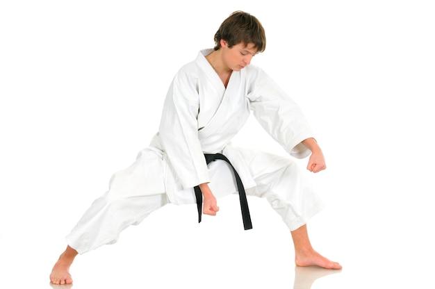 Młody, utalentowany profesjonalny karate w garniturze kimono z czarnym paskiem pozuje do walki