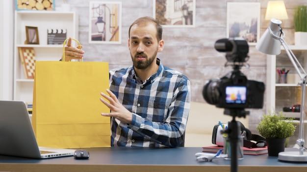Młody vloger prezentuje specjalny upominek dla swoich obserwatorów. znany influencer. twórca treści kreatywnych.