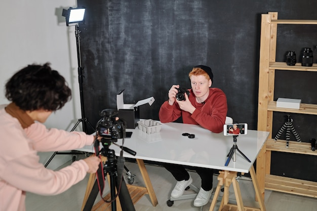 Młody vlogger w swobodnym swetrze i czapce pokazuje swój nowy aparat fotograficzny podczas kręcenia filmów w studio
