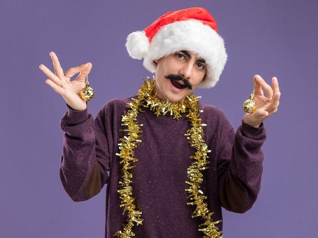 Młody wąsaty mężczyzna w świątecznym kapeluszu mikołaja z blichtrem na szyi, trzymający bombki z szczęśliwą twarzą, uśmiechający się radośnie stojąc nad fioletową ścianą