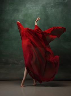 Młody wdzięczny baleriny przetargu na ciemnozielonej przestrzeni studio z czerwonym suknem