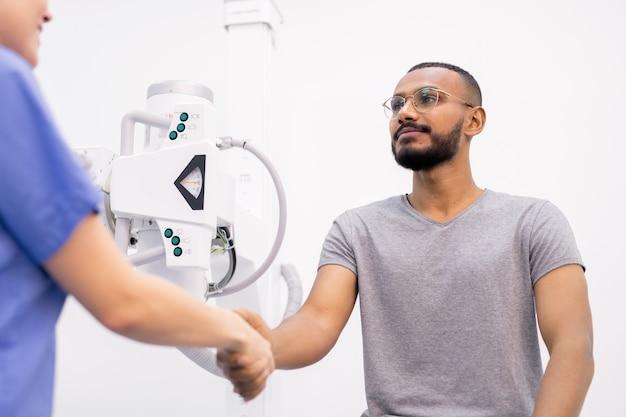 Młody wdzięczny pacjent międzykulturowy ściskający rękę swojemu lekarzowi lub pielęgniarce po wyzdrowieniu w nowoczesnych klinikach