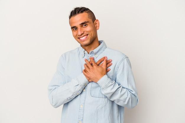Młody wenezuelczyk na białej ścianie ma przyjazny wyraz twarzy, przyciskając dłoń do klatki piersiowej. koncepcja miłości.