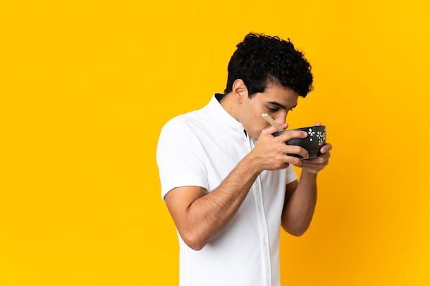Młody wenezuelczyk na żółtym tle trzyma miskę makaronu pałeczkami i je go