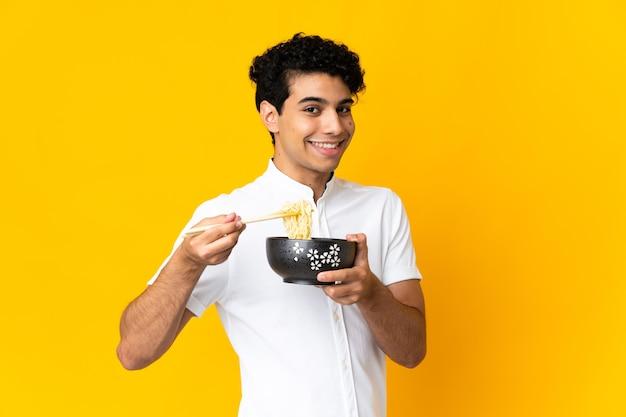Młody wenezuelczyk na żółtym tle trzyma miskę makaronu pałeczkami