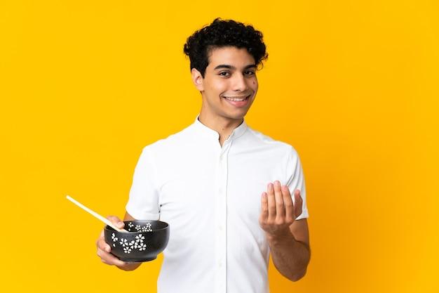 Młody wenezuelczyk na żółtym tle, zapraszający do pomocy. cieszę się, że przyszedłeś z miską makaronu pałeczkami