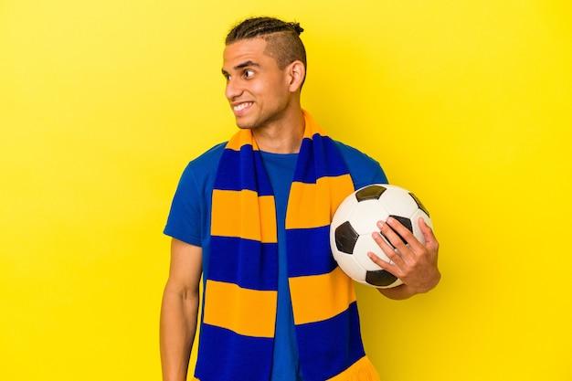 Młody wenezuelczyk oglądający piłkę nożną na białym tle na żółtym tle wygląda na uśmiechnięty, wesoły i przyjemny.