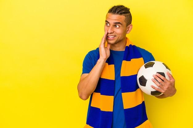 Młody wenezuelczyk oglądający piłkę nożną na żółtym tle mówi tajne gorące wiadomości o hamowaniu i patrzy na bok