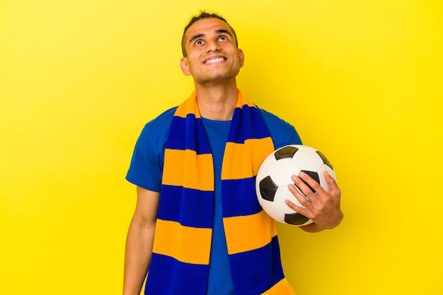 Młody wenezuelczyk oglądający piłkę nożną odizolowaną na żółtej ścianie, marzący o osiągnięciu celów i celów