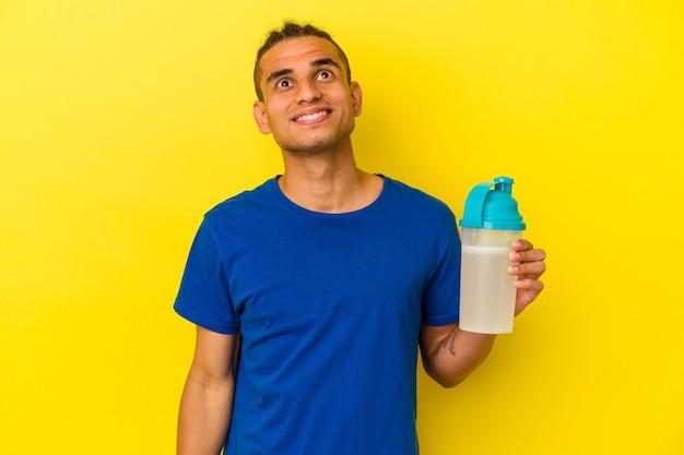 Młody wenezuelczyk pijący koktajl proteinowy na żółtym tle, marzący o osiągnięciu celów i celów