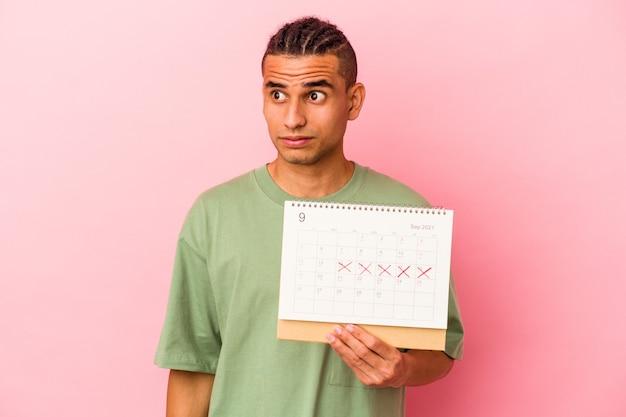 Młody wenezuelczyk trzymający kalendarz na różowej ścianie zdezorientowany, czuje się niepewny i niepewny.