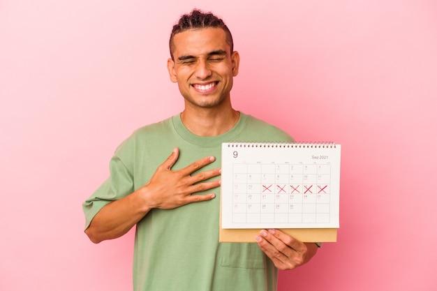 Młody wenezuelczyk trzymający kalendarz na tle różowej ściany śmieje się głośno, trzymając rękę na piersi.