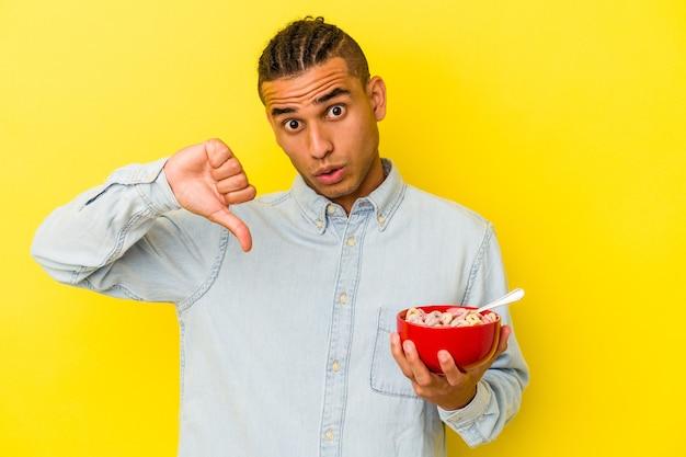 Młody wenezuelczyk trzymający miskę zbóż na żółtym tle