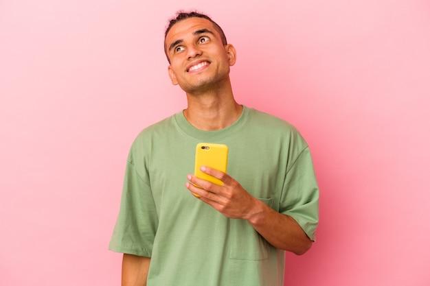 Młody wenezuelczyk trzymający telefon komórkowy odizolowany na różowej ścianie, marzący o osiągnięciu celów i celów