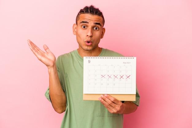 Młody wenezuelski mężczyzna trzyma kalendarz na białym tle na różowej ścianie zaskoczony i zszokowany.