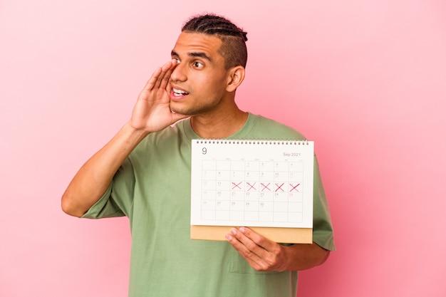 Młody wenezuelski mężczyzna trzyma kalendarz na białym tle na różowym tle krzycząc i trzymając dłoń w pobliżu otwartych ust.