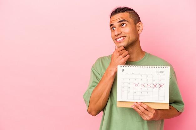 Młody wenezuelski mężczyzna trzyma kalendarz na białym tle na różowym tle, patrząc w bok z wyrazem wątpliwości i sceptycyzmu.