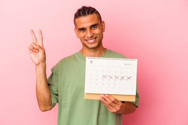 Młody wenezuelski mężczyzna trzyma kalendarz na białym tle na różowym tle radosny i beztroski pokazujący palcami symbol pokoju.
