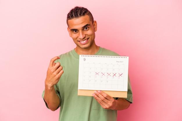 Młody wenezuelski mężczyzna trzyma kalendarz na białym tle na różowym tle, wskazując palcem na ciebie, jakby zapraszając podejdź bliżej.