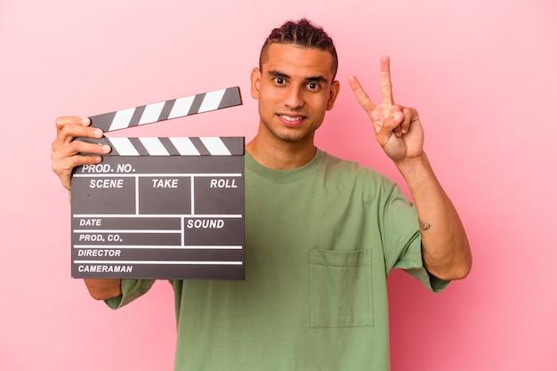 Młody wenezuelski mężczyzna trzyma klaps na białym tle na różowym tle pokazując numer dwa palcami.