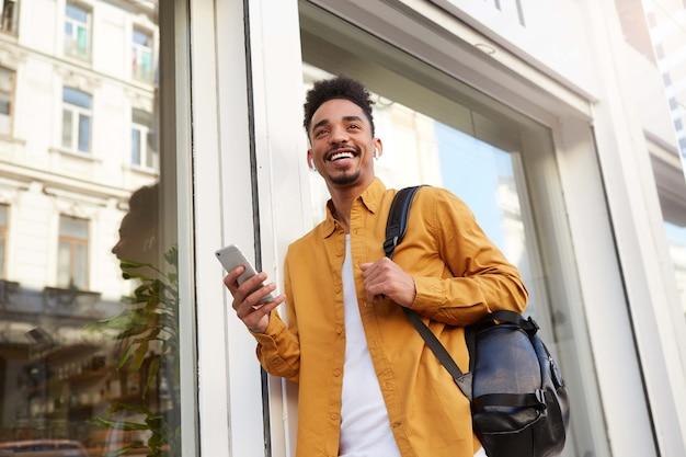 Młody wesoły afroamerykanin w żółtej koszuli, wygląda na szczęśliwego i szeroko uśmiechniętego, idzie ulicą i trzyma telefon, słucha swojej ulubionej piosenki na słuchawkach. v