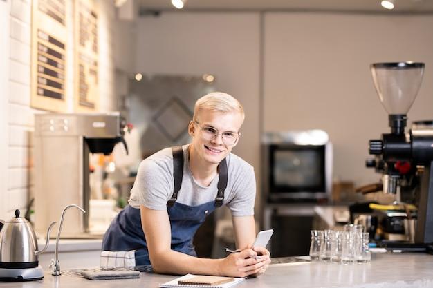 Młody wesoły barista w roboczym ubraniu patrzy na ciebie pochylając się nad stołem i przeglądając zamówienia klientów na smartfonie