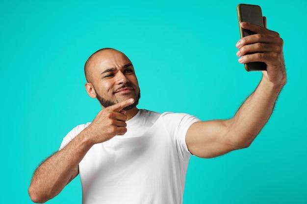 Młody wesoły człowiek afroamerykanin biorąc zdjęcie selfie