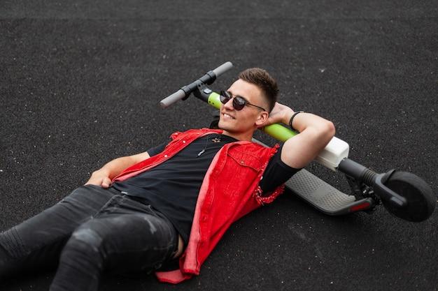 Młody wesoły człowiek hipster w stylowe okulary przeciwsłoneczne w modnych jeansowych czerwono-czarnych ubraniach leży na skuterze elektrycznym na boisku do koszykówki